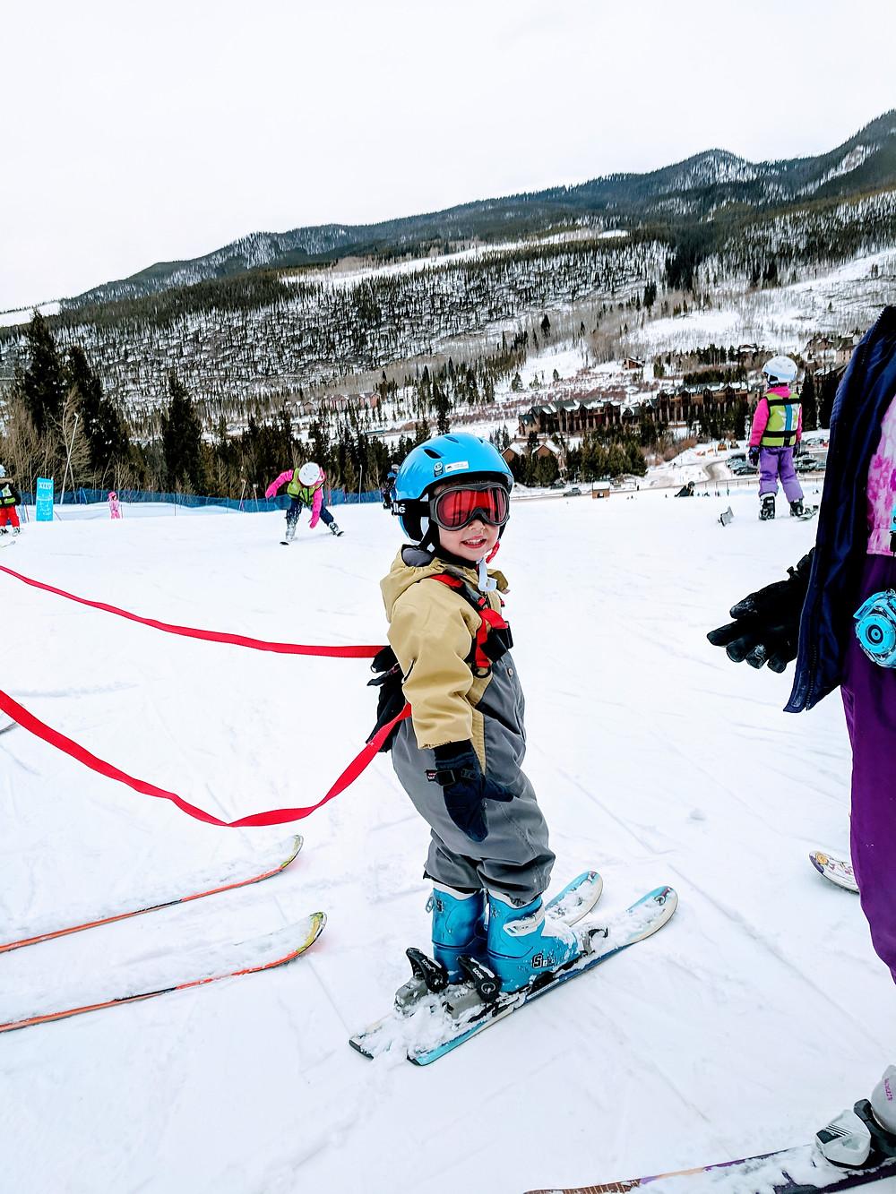 Child skiing at ski resort with harness