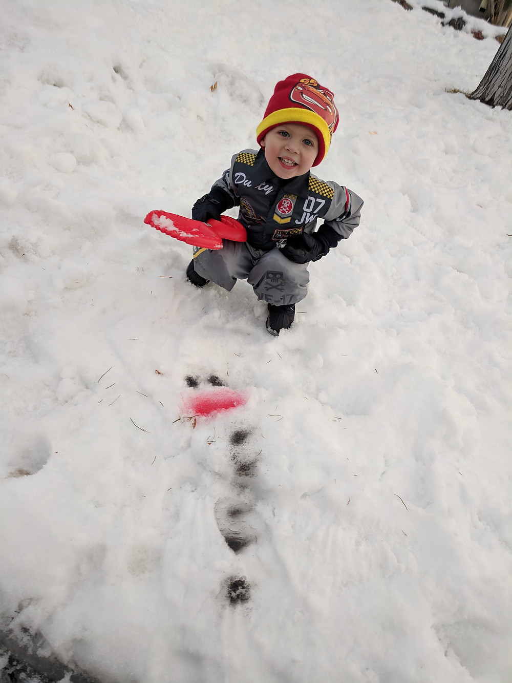 Child playing in snow making snowman