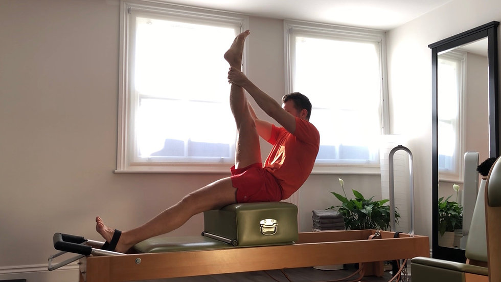 Tree exercise on the Pilates reformer to stretch the back and hamstrings