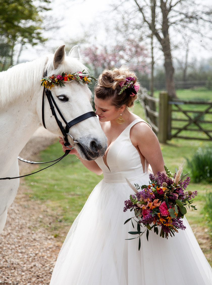 Bride and her horse on an outdoor wedding day, country and boho inspired