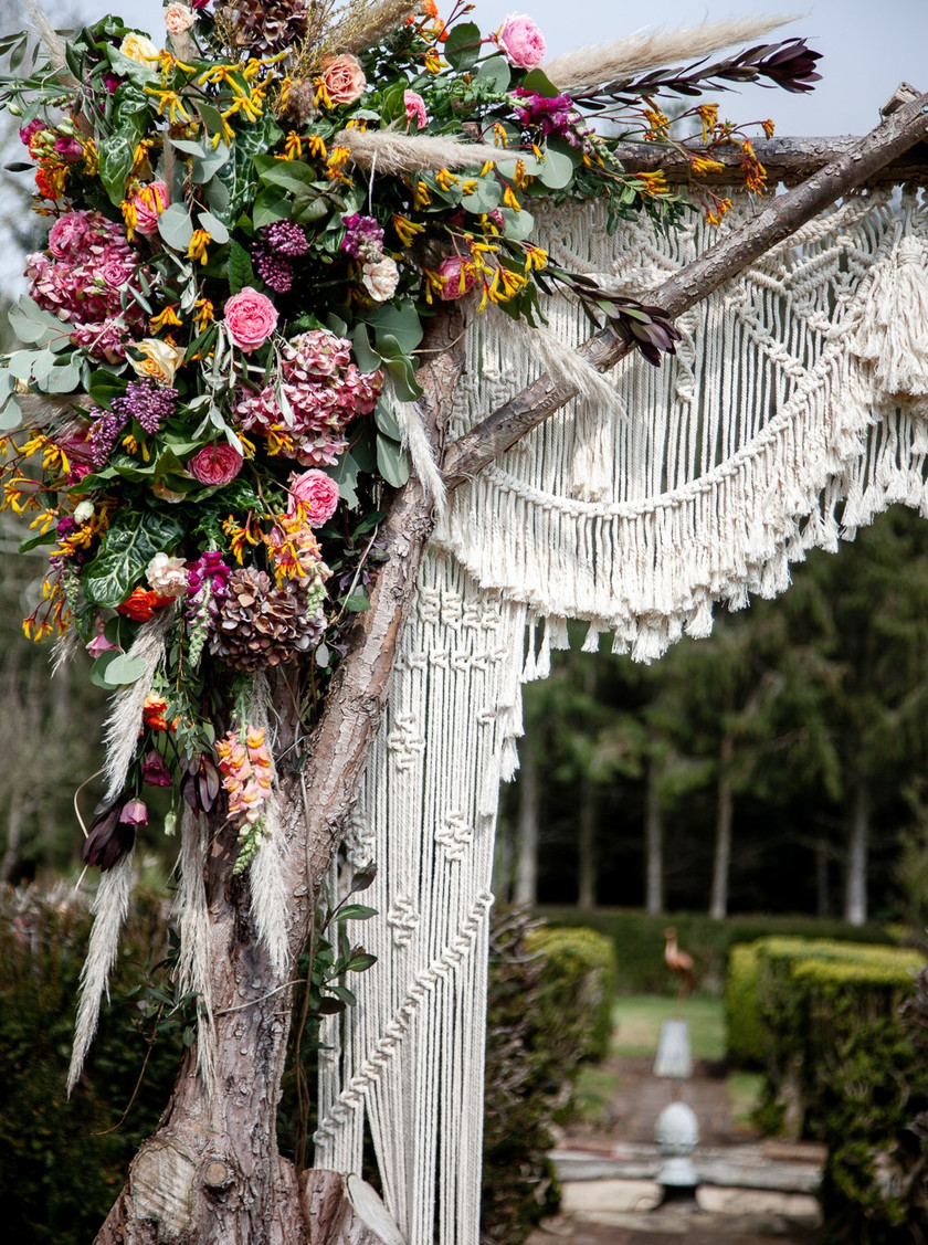 Macrame backdrop archway, filled with aztec inspired flowers. Wedding outside
