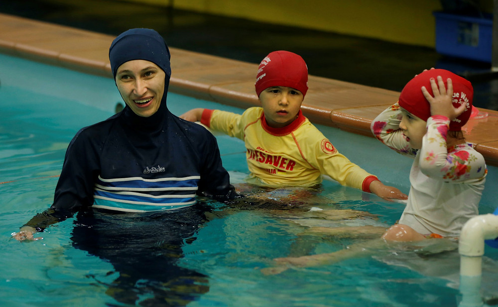 Photo of a woman and 2 children swimming from https://womenintheworld.com/2017/05/17/australian-swimming-center-begins-offering-ladies-only-swimming-hours-for-muslim-women/