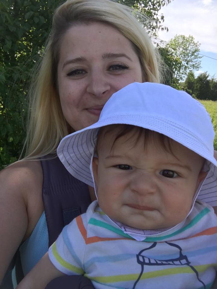 Ellen Spivey walking with her son Ethan in a baby carrier