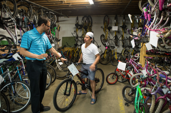 Board Member and Latino Night Coordinator Miguel Aranda assists patron at Bike Co-op
