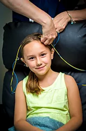 little girl being hooked up.png