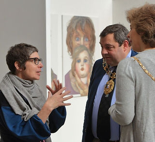 Artist Sonia Boue talking to the Mayor and Mayoress of Oxford with an image of a woman's face on the wall behind them