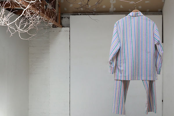 An installation artwork by Sonia Boue with pyjamas on a hanger and painted twigs.