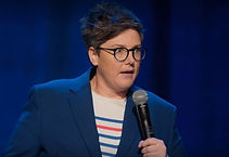 A woman with short hair and glasses speaking into a microphone