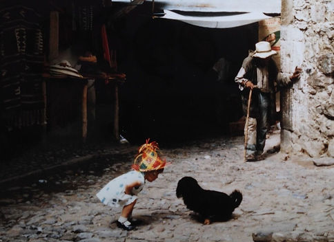 Toddler Sonia wearing white dress & straw hat talking to a black dog in Puebla, Mexico.