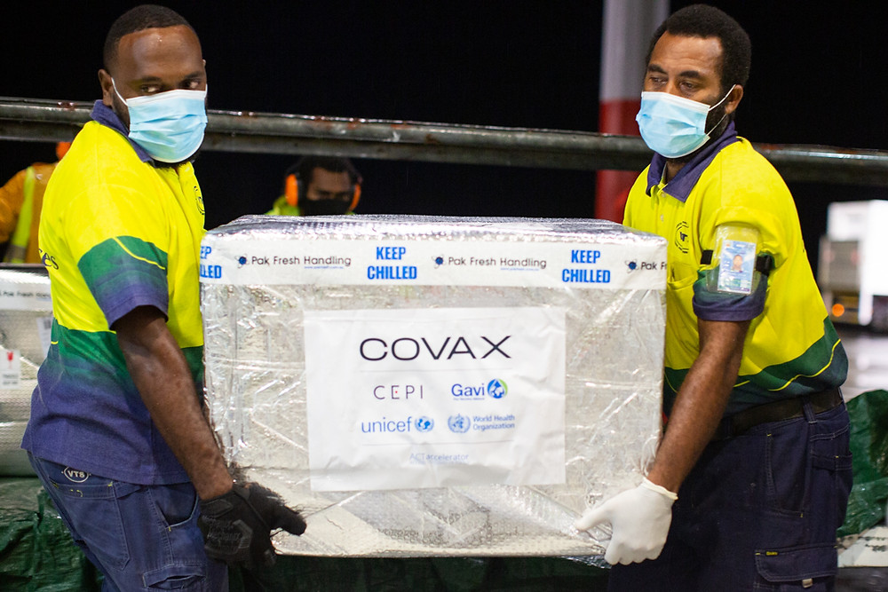 Men carrying a COVAX tagged box containing COVID-19 vaccines.
