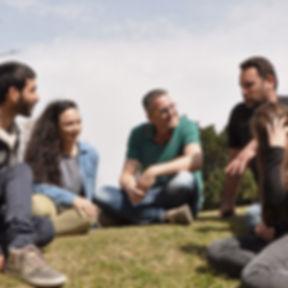 A photo of people sitting and talking on a  lawn