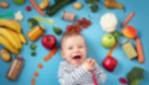 baby surrounded with fruits and vegetabl