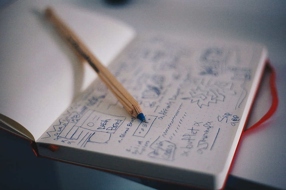 A notebook filled with doodles sits open on a table with a pen.