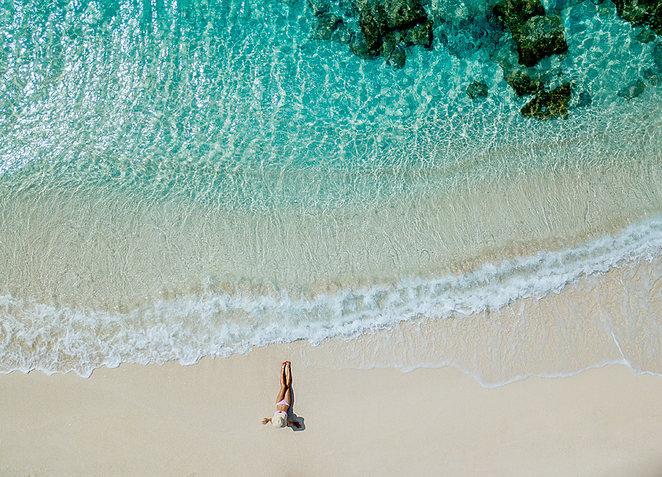 Woman on beach in Bimini Bahamas  by Jenny Schartner