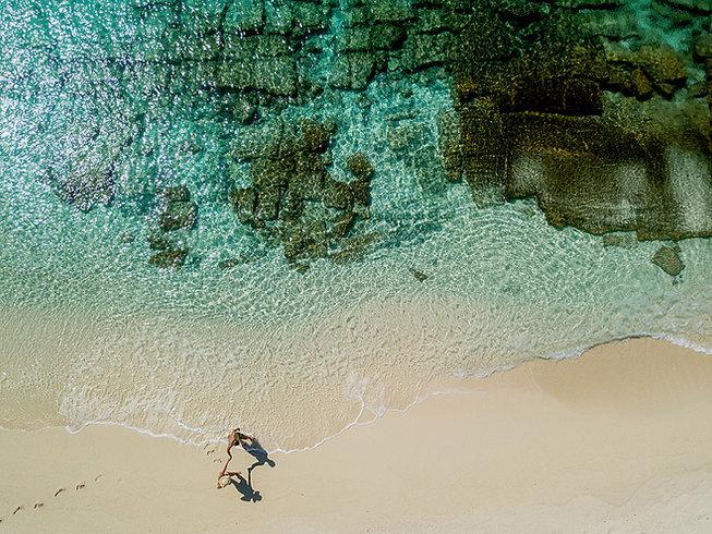 Drone shot Couple walking on beach