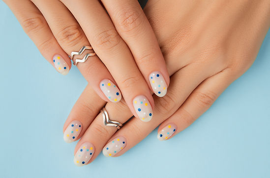 womans-hands-with-trendy-polka-dot-summer-manicure-blue-background.jpg