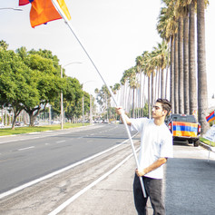 Young Armenian proudly holds the Armenian Flag attracting the attention of passing cars on Glenoaks Blvd., Glendale, Calif., Thursday, Oct. 8, 2020