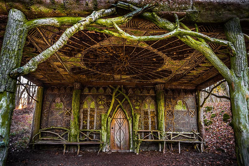 """A """"Globe Theatre"""" constructed in the woods out of intertwined branches, featuring a frons scenae and the """"heavens"""" canopy made of patterns of sticks."""