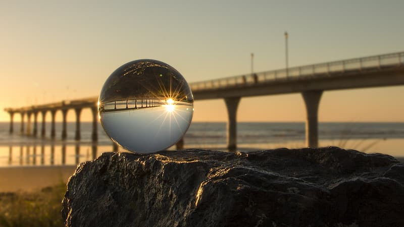 A concrete bridge over a river. In the foreground, a glass sphere inverts the bridge and reflects the sky and the sun.