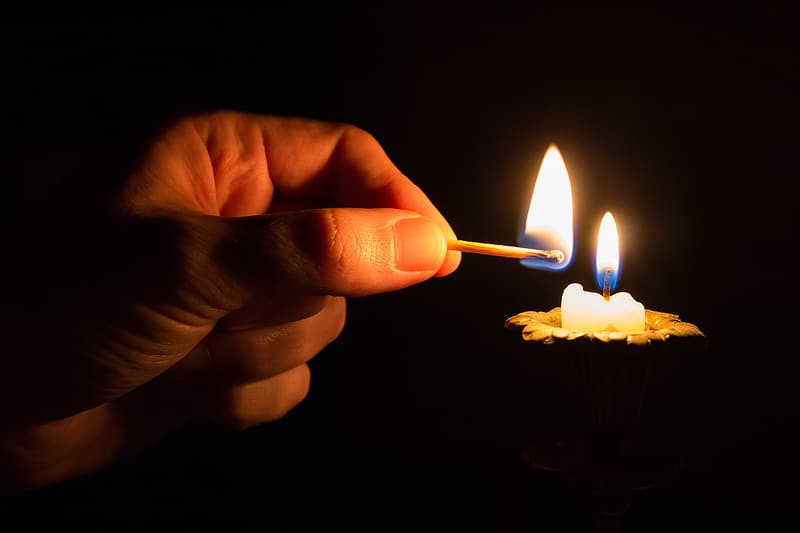 Person lighting a candle.