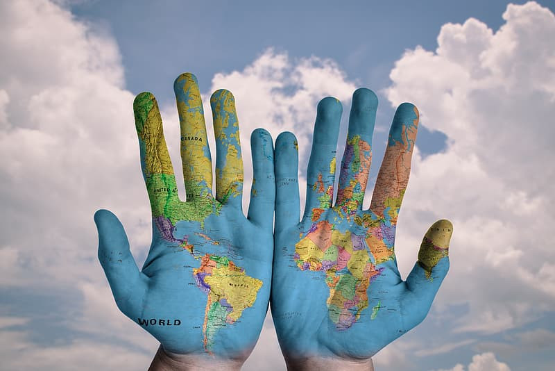 Hands painted with the world map, featuring South America and Africa.