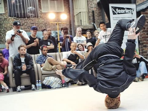 An audience watches a B-Boy execute a headspin