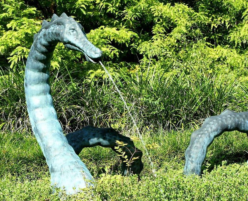 A bronze serpent fountain in a green garden.