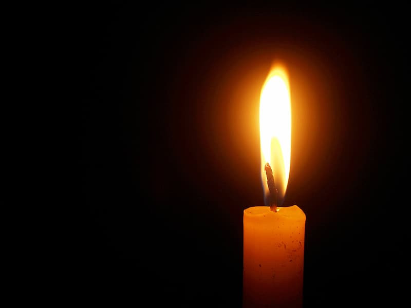 a lit candle against a dark background