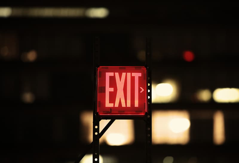 Red Exit sign pointing to the right against a dark background.