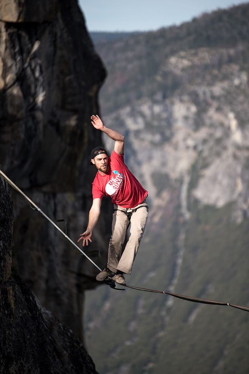 A man in a red shirt balances on a tight rope high in the mountains.