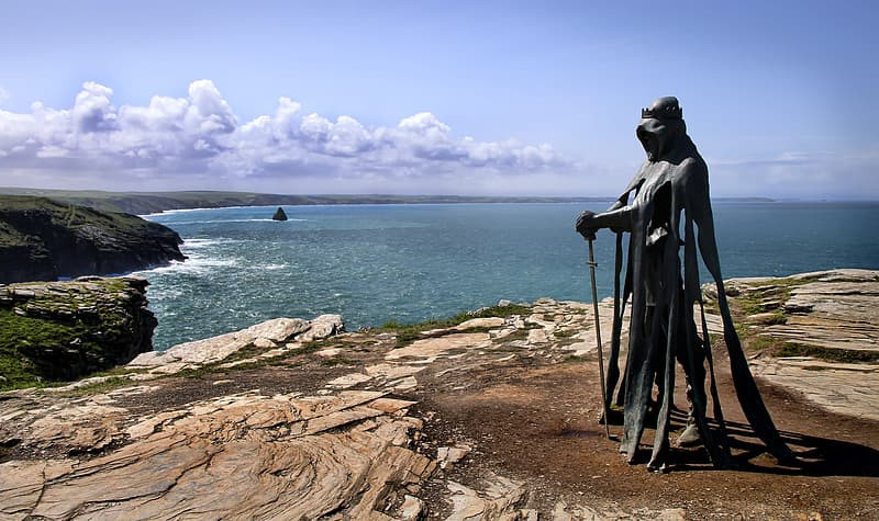 Green copper statue of King Arthur on a rocky cliff above the sea