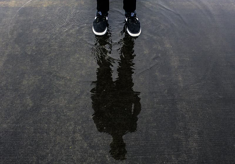 person's feet in running shoes, standing in water on cement, with a focus on their reflection