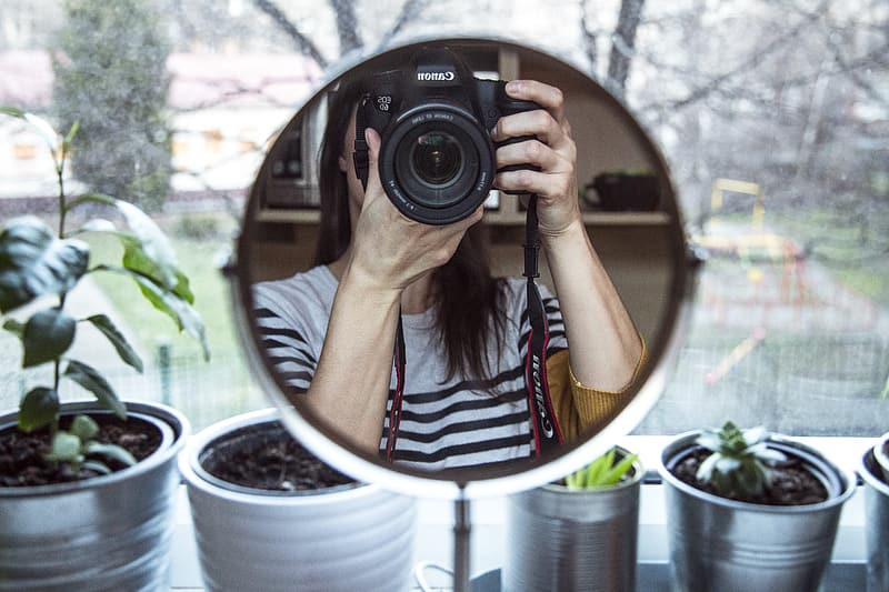 A woman taking a picture of herself in a round mirror in front of potted plants