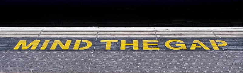 Subway platform sign reading: MIND THE GAP