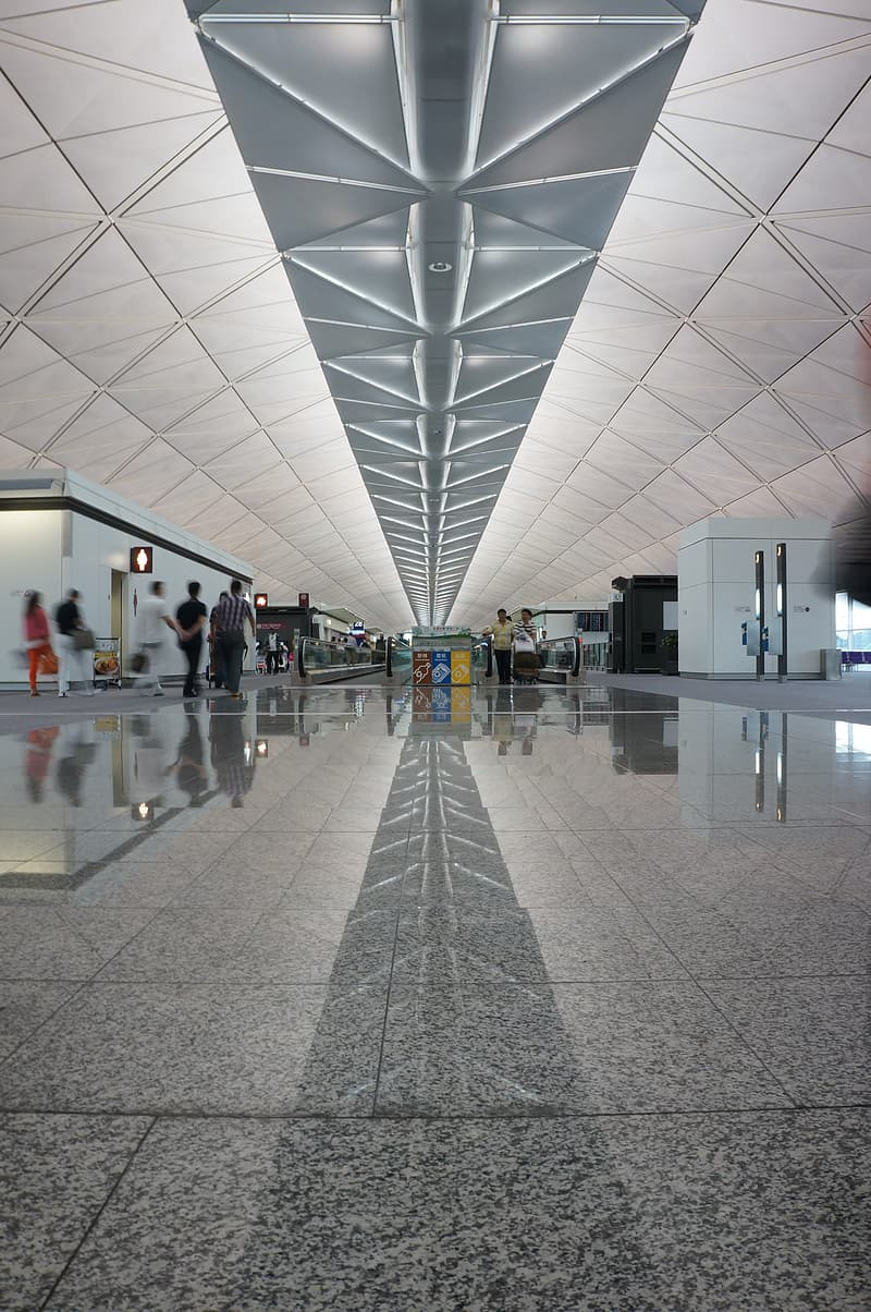 Airport terminal featuring overhead lights that form the shapes of arrows that are reflected on the floor, directing traffic along the path through the space.