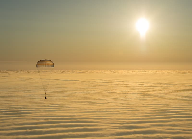 Space capsule on a parachute drifts over the ocean at sunset.