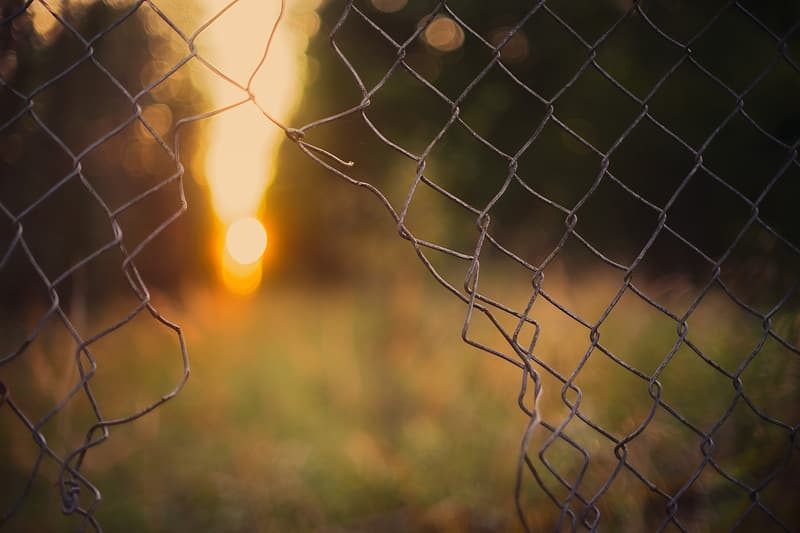 A broken chain link fence with the sunrise in the background.