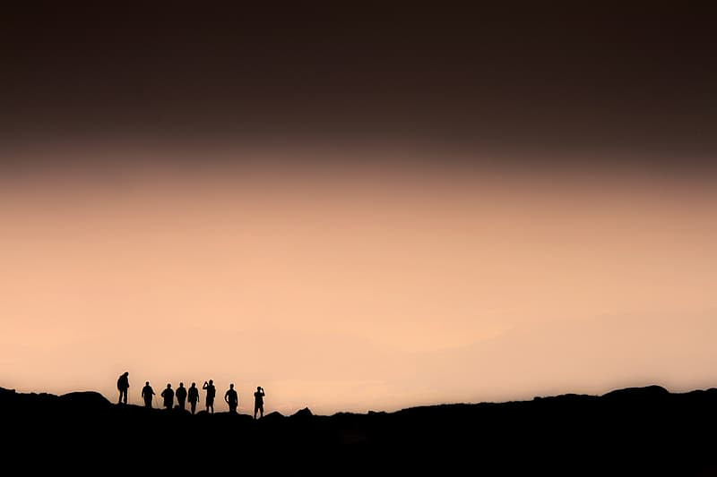 People stand in a line on a ridge, silhouetted against a large, blank, sepia-toned sky.