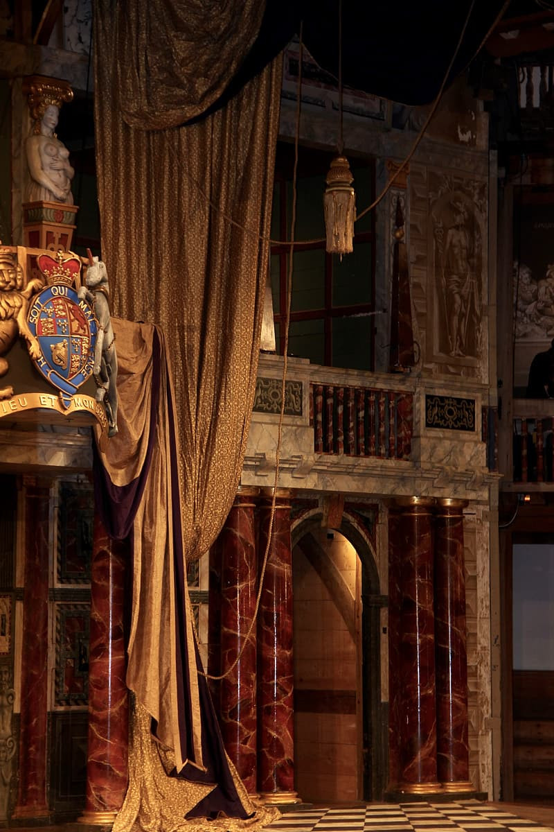 The Globe Theatre Frons Scenae door and Lords' Room draped with curtains and coat of arms.