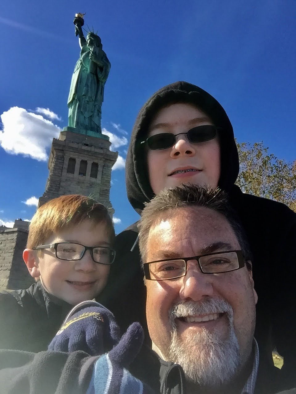 A photo of david brodosi and his two sons of the Statue of Liberty