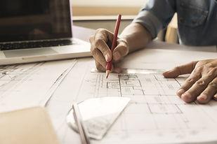 Hands of Engineer working on blueprint,C