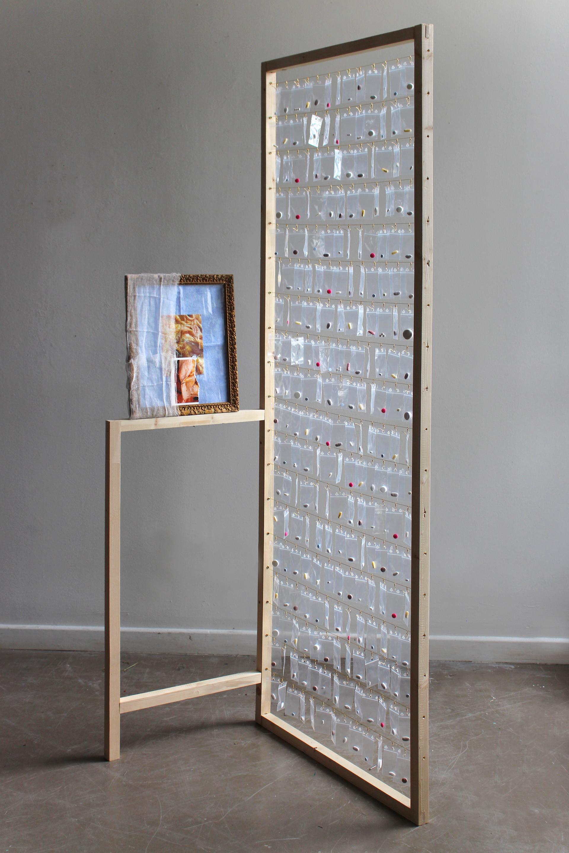 Étalage Thérapeuthique / bois, sachet plastique, pillules, cadre, tissu, photo, fils, fermoirs / H200xL100xP40cm, 2018, Caen.