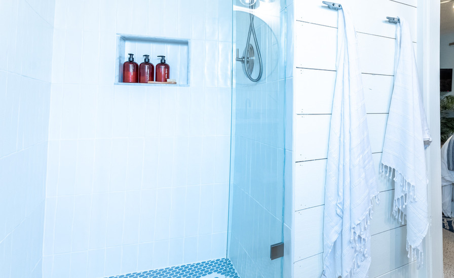We expanded the shower width and height-wise, adding a spa-like shower rain head, and custom glass shower to make everything much lighter.