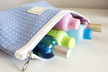 Blue travel toiletry bag with travel toiletries, small plastic bottles of hygiene products