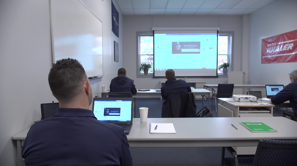 Four team members at Port Harbor Marine participate in the Dealer Week education online via a large screen and individual note pads in 2020.