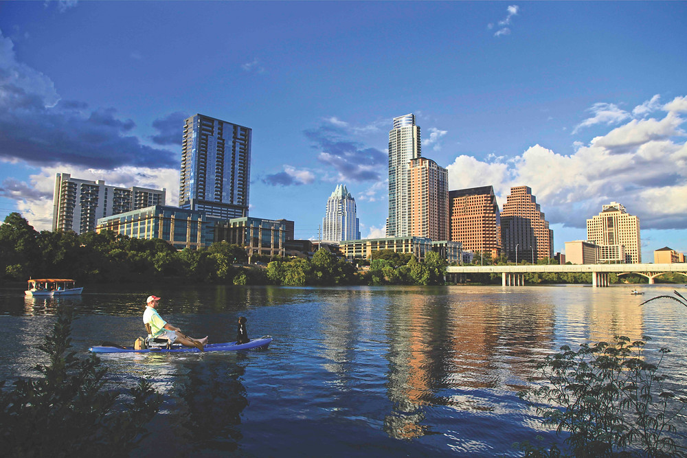 A water view of the Austin skyline with a man paddling with a dog and boat in the background.