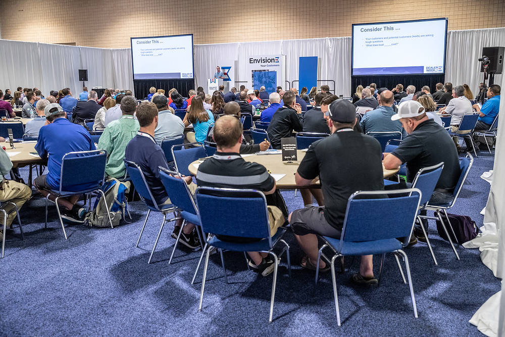 Attendees of Dealer Week, a marine industry conference and expo sitting in chairs at tables listening to an educator on stage.