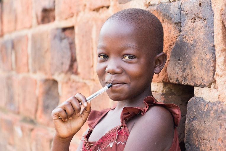 An 11-year-old Ugandan girl smiling, hol