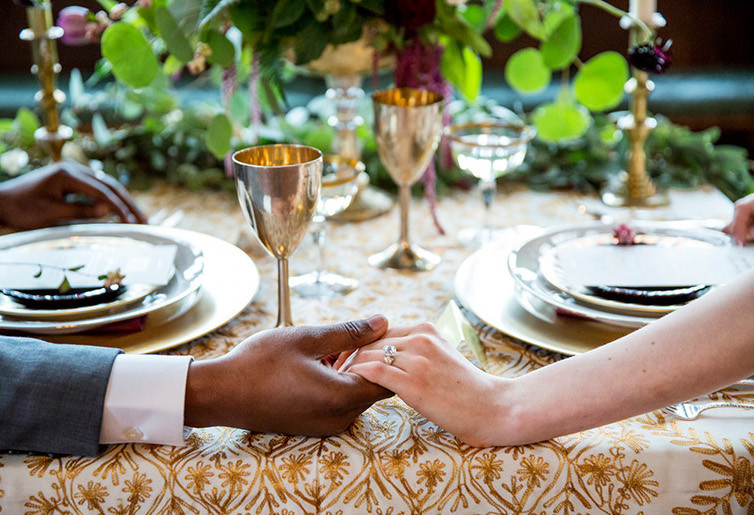 couple holding hands, wedding ring, diamond ring, engagement ring, bridal set, plates, wedding dinner, bride and groom, metal chalice, metal goblets, exotic wedding, gold tablecloth, gold and ivory, gold candlesticks, wedding table, wedding centerpiece, biracial couple, exotic wedding decor, eco chic wedding, boho wedding style,