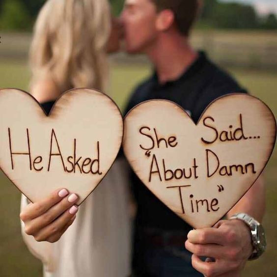 engagement photo idea, wooden hearts, wooden placards, happy couple, kissing couple, watch, wristwatch, engagement photo ideas